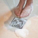 Füße einer Person am Duschbalauf in der Dusche