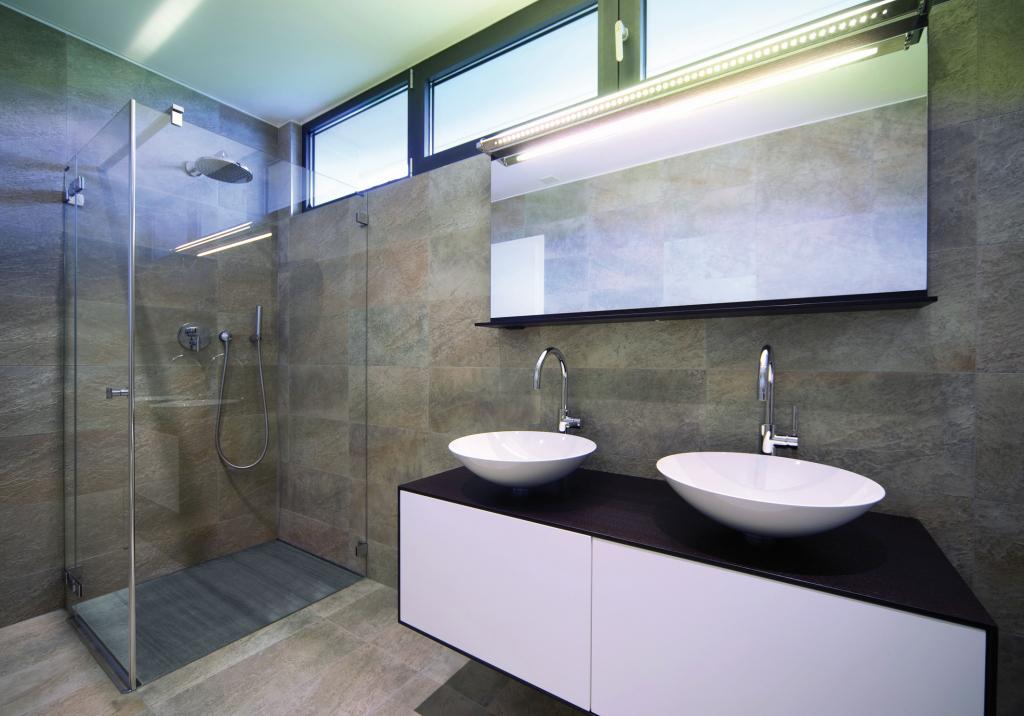 Badezimmer mit bodengleicher Dusche, daneben zwei Waschbecken.