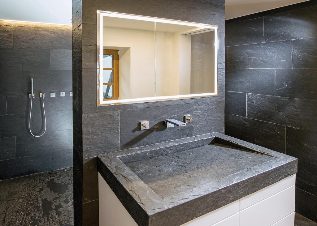 Edles Badezimmer mit bodengleicher Dusche und dunklem Waschbecken aus Marmor.