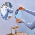 Spiegel wird ohne Bohren von einer Frau an Badfliesen angebracht