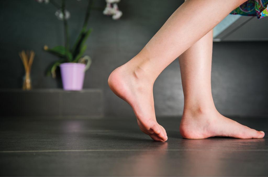 Nackte Füße auf dem Fußboden.