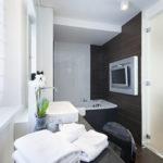 Modernes und komfortables Badezimmer mit Badewanne, Waschbecken, Ablage, Stuhl und TV