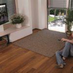 Junge Frau bedient die Jalousien mit einer Fernbedienung, um Spiegelungen im TV zu vermeiden.