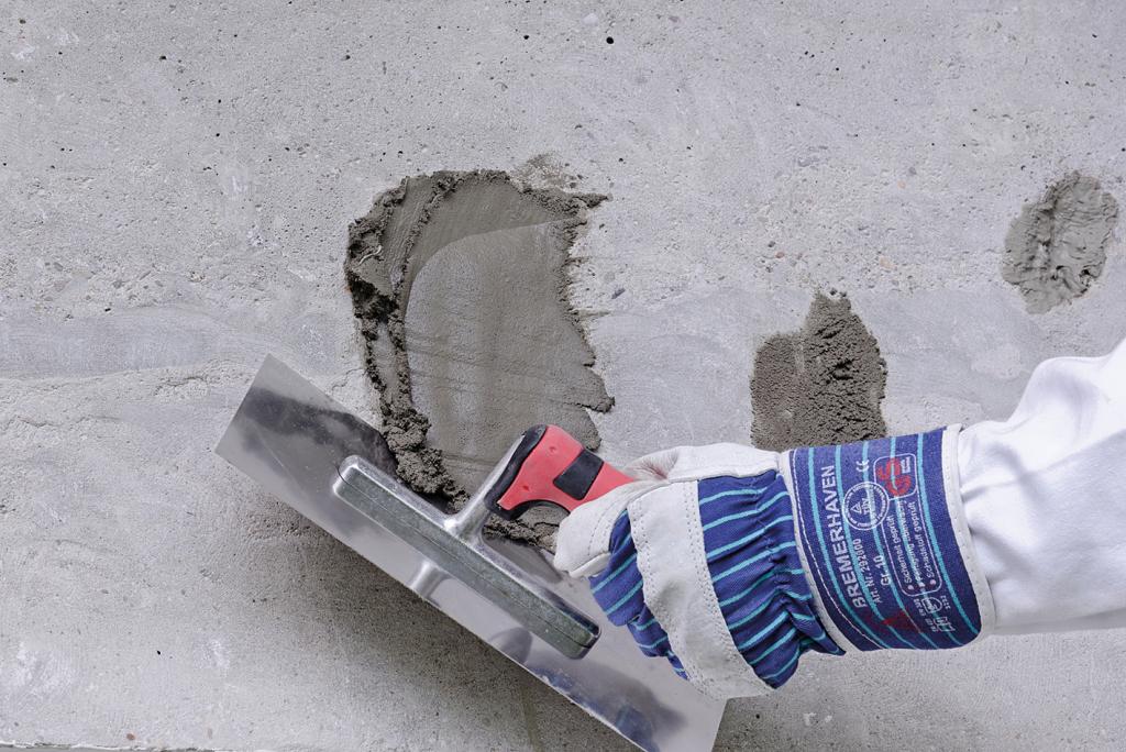 Gerissene Stellen im Beton werden mit Mörtel zugemacht. So kann man schnell den Beton ausbessern.