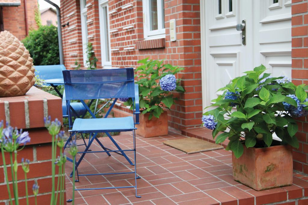 Eine Treppe im Eingangsbereich vor dem Haus wurde mit Fliesen belegt. Kontraste setzen farbige Blumen und Stühle.