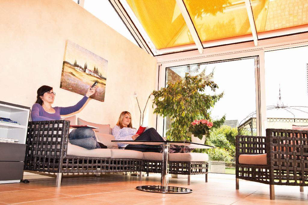 Frau bedient den automatischen Sonnenschutz im Wintergarten mit einer Fernbedienung