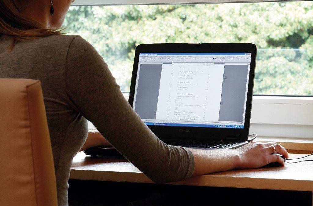 Frau sitzt im Home Office am Computer, sie wird durch Rollladen nicht geblendet.
