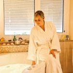 Frau im Bademantel auf dem Badewannenrand bei geschlossenen Rollläden.