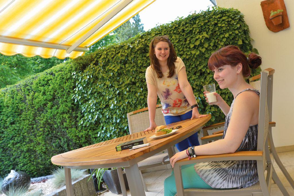 Zwei junge Frauen auf der Terrasse unter der Markise. Sie sind geschützt durch Sonnenschutz.