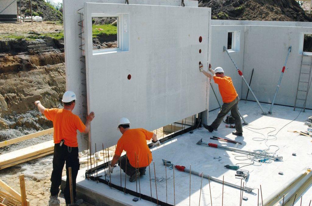Bauarbeiter bauen den Keller mit Betonfertigteilen