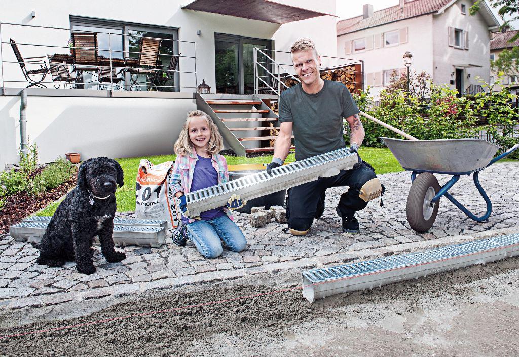 Vater baut mit seiner kleinen Tochter auf der Terrasse eine Terrassenentwässerung ein. Es handelt sich um eine Entwässerungsrinne. Ein Hund sitzt dabei.