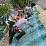 Drei Arbeiter dämmen ein Steildach mit Dachfolie
