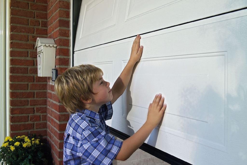 Kind schiebt das Garagentor zu. Vorsicht Gefahr durch fehlende Sicherheit.
