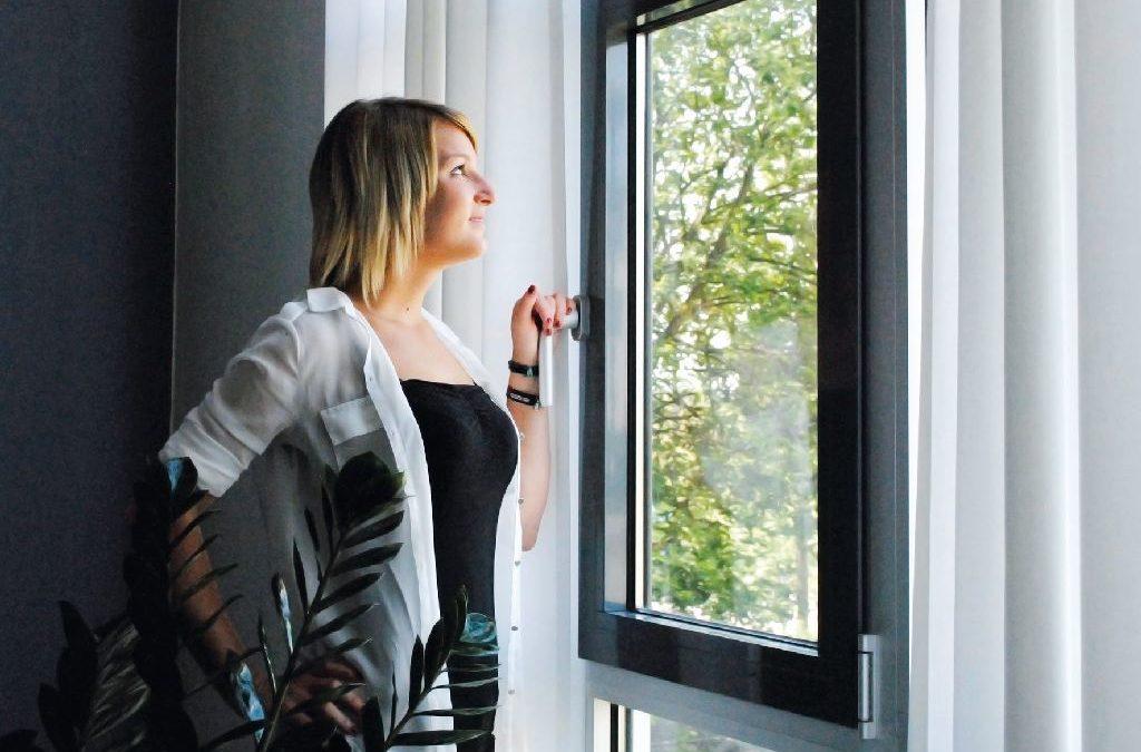 Junge Frau steht am Fenster. Eine Lüftungsanlage im Raum sorgt für angenehmes Raumklima.