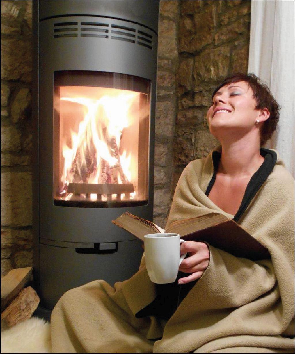 Frau sitzt mit einem Buch vor einem brennenden Ofen. Die Heizungsanlage funktioniert dank Fachmann.