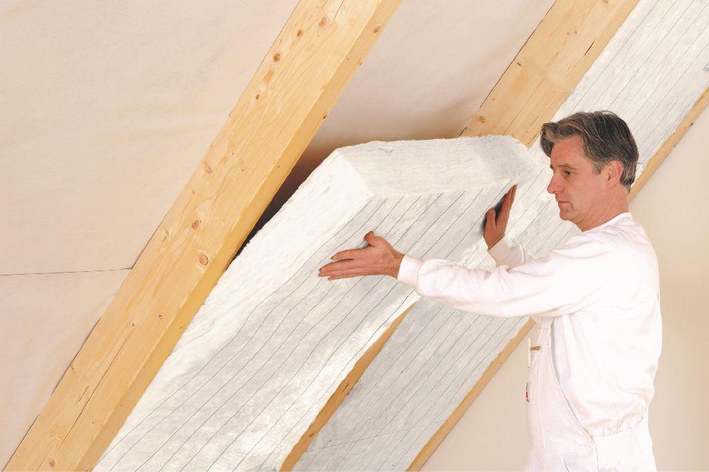 Mann dämmt ein Dach im Innenraum mit einem Dämmstoff aus Mineralwolle.