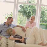 glückliche Familie auf dem Sofa, im Hintergrund große Fensterflächen