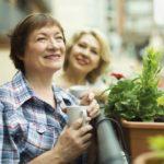 Zwei Frauen trinken Kaffee auf dem Balkon im Mehrfamilienhaus. Sie sind zufrieden über die energetische Sanierung.