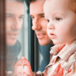 Vater und kleiner Sohn sehen aus einem Fenster.