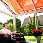 Mann sitzt mit Kopfhörern im Wintergarten.