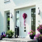 Weißes Haus mit weißer Haustür, Fenstern und Steintreppe. Blumenkübel schmücken den Eingangsbereich (Details der Haustüren entscheiden über die Wirkung)