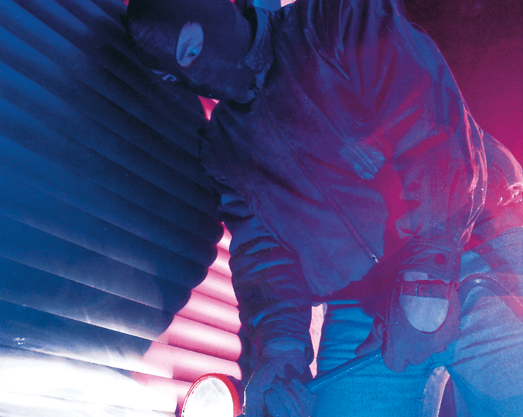 Einbrecher mit Sturmmaske und Taschenlampe versucht mit einem Kuhfuss einbruchhemmende Rollläden aufzuhebeln.