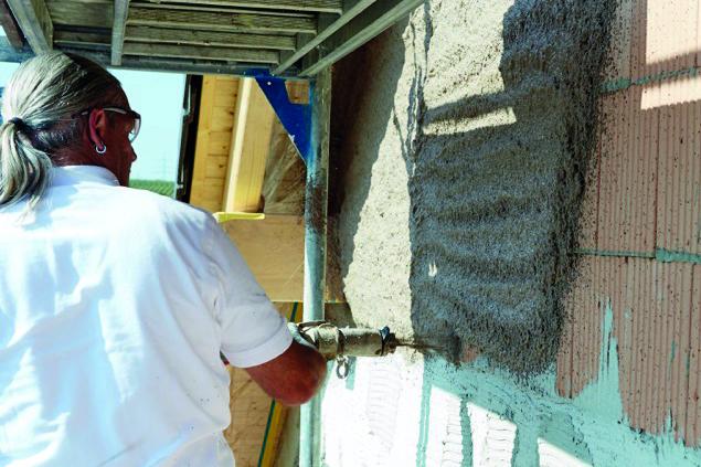 Handwerker bearbeitet Fassade, die mit einem Leichtputz modernisiert wird.