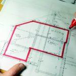 Planung des Traumhauses: mit einem roten Edding wird ein Grundriss markiert.