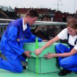 Zwei Auszubildende vermessen mit einem Zollstock etwas auf dem Dach. (Handwerk und das Dach)