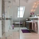 Bad unter dem Dach mit einer neuen Dusche und gläserner Duschkabine.