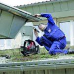 Fachmann im Blaumann überprüft die Metallbauteile am Dach.