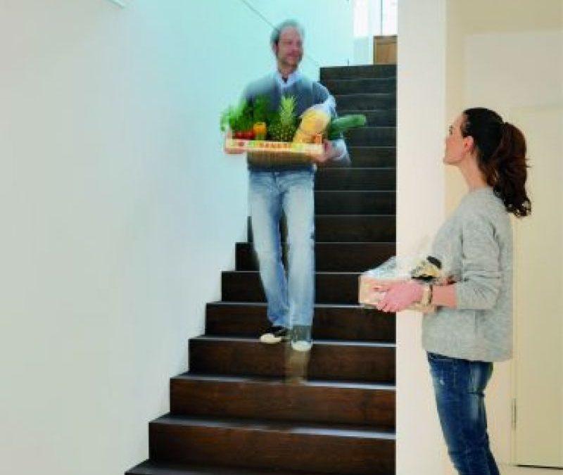 Eine Betontreppe mit Holz verkleidet. Ein Mann geht die Treppe runter und trägt dabei den Einkauf runter