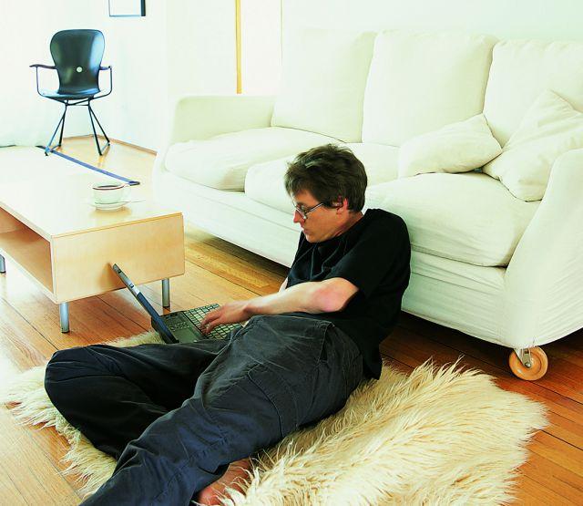 Trotz Altbauten: Ein Mann liegt entspannt und barfuß auf einem Teppich im Wohnzimmer und benutzt einen Laptop