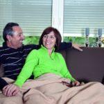 Niedrige Heizkosten dank Rollläden: Ein glückliches Ehepaar sitzt gemeinsam auf einem Sofa