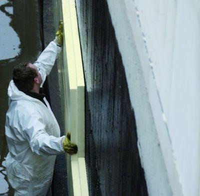 Ein Facharbeiter installiert eine Perimeterdämmung