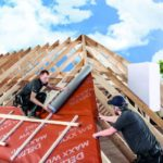 Zwei Facharbeiter kümmern sich um die Dachdeckung von einem neu gebauten Bungalow