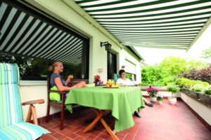 Zwei Frauen sitzen sonnengeschützt auf einer Terrasse, dank einer Markise.