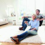 Ein Paar lässt sich im Wohnzimmer von der Sonne bestrahlen