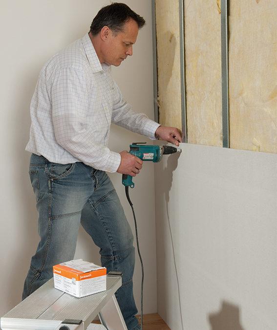 Ein Heimwerker dämmt seinen Keller mit praktischen Gipsfaser-Platten