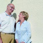 Ein glückliches Ehepaar steht gemeinsam vor ihrer neu gestalteten Hausfassade.