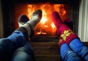 Der richtige Brandschutz macht es möglich: Zwei Personen wärmen sich ihre Füße vor einem Kamin.