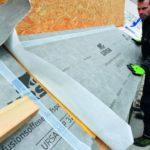 Ein Facharbeiter dämmt und prüft das Hausdach. Eine regelmäßige Prüfung ist besonders wichtig.