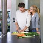 Ein Paar kocht gemeinsam in ihrem Eigenheim. Dank der richtigen Wahl der Baustoffe, genießen sie ein angenehmes Raumklima.