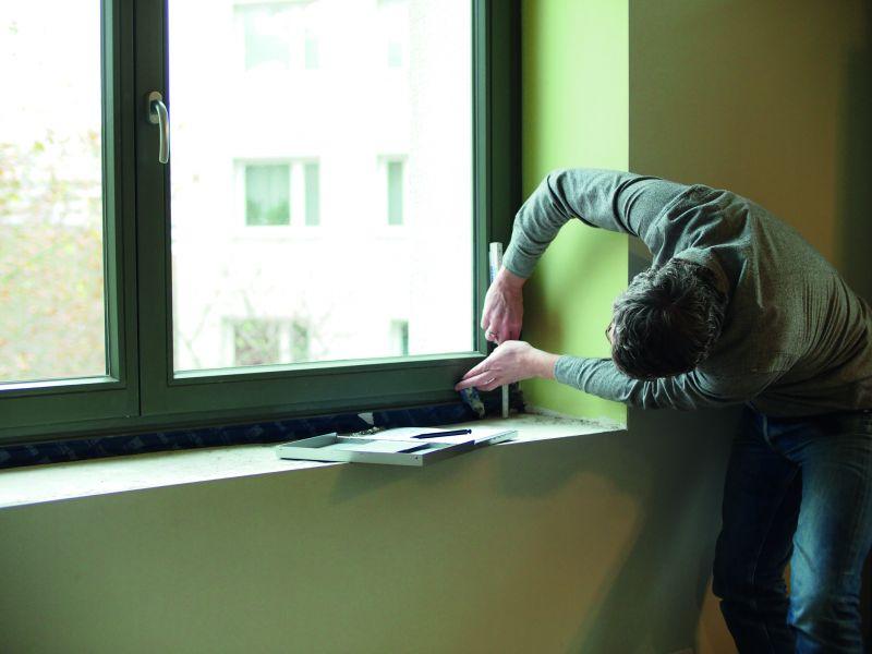 Ein Mann ermittelt mit einem Zollstock die Maße eines Fensters (Fenstertausch).