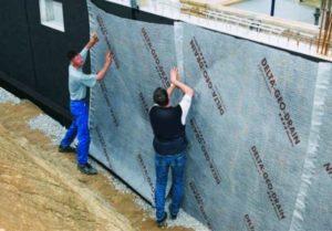 Zwei Bauherren dichten die Wände eines Hauses ab (gesunde Raumluft im Keller).