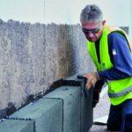 Ein Facharbeiter verlegt nicht brennbare Elemente an einer Hausfassade. (brandsicher)