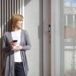 Eine Frau hält ein Glas Wein in der Hand und schaut aus dem Fenster. (Schallschutz)