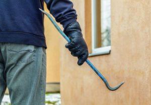 Ein Mann trägt einen schwarzen Handschuh, hält eine Brechstange in der Hand und sein Blick ist auf ein geschlossenes Fenster gerichtet.