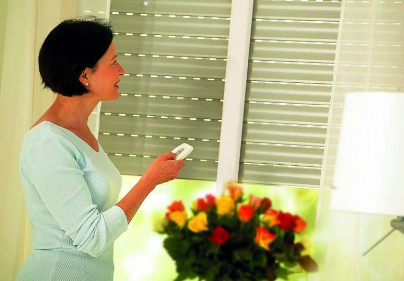 Eine Frau steuert per Fernbedienung ihren Rollladen.
