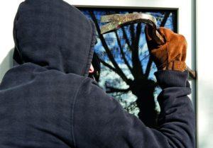 Ein Einbrecher versucht ein Fenster aufzustemmen. (Fenster planen)